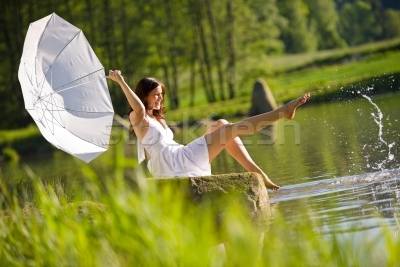 137768_stock-photo-happy-romantic-woman-sitting-by-lake-splashing-water